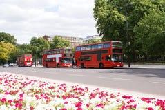 Calle, autobuses de dos plantas rojos, y coches en Londres, Inglaterra Imágenes de archivo libres de regalías
