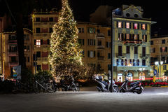 Calle central de la noche con el árbol de navidad y las motos parqueadas debajo de él Imagen de archivo libre de regalías