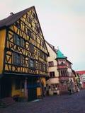 Calle central del pueblo de Riquewihr en Alsacia, Francia con las casas de entramado de madera tradicionales coloridas fotografía de archivo libre de regalías