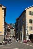 Calle colorida con los edificios viejos y gente en Annecy Imagen de archivo libre de regalías