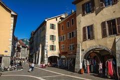 Calle colorida con los edificios viejos y gente en Annecy Foto de archivo