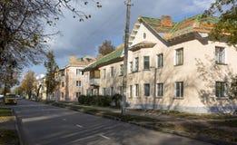 Calle con edificios de dos pisos rosados y el camino delante de Fotos de archivo libres de regalías