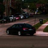 Calle con la conducción de automóviles y coches en el lado del camino imagen de archivo