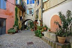 calle con las flores en la ciudad vieja Coaraze en Francia Imágenes de archivo libres de regalías