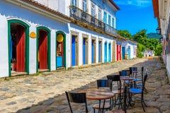 Calle con las tablas de café en centro histórico en Paraty, Rio de Janeiro, el Brasil foto de archivo