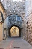Calle con los arcos en el pueblo de Castries, Francia Foto de archivo libre de regalías