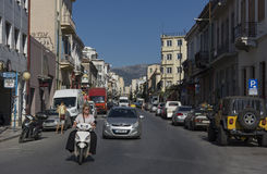 Calle con un camino ancho, con las casas por ambas partes, coches, bicis Imágenes de archivo libres de regalías