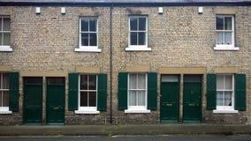 Calle con una fila de casas colgantes viejas británicas típicas con las puertas verdes y de obturadores de la ventana en durham I Foto de archivo libre de regalías