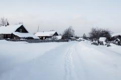 Calle cubierta con nieve en pueblo ruso tradicional Imagen de archivo