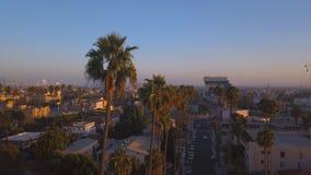 Calle de Beverly Hills con las palmeras en la puesta del sol en Los Angeles almacen de metraje de vídeo