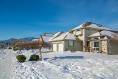 Calle de casas residenciales en nieve el día soleado del invierno Foto de archivo libre de regalías