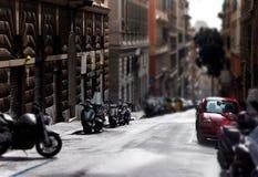 Calle de la ciudad con los coches y los motocycles estacionados Fotos de archivo libres de regalías
