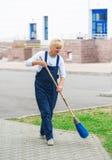 Calle de la ciudad de la limpieza del trabajador del barrendero con la herramienta de la escoba imagenes de archivo