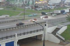 Calle de la ciudad después de fuertes lluvias y de coches que la mueven encendido foto de archivo libre de regalías