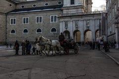 Calle de la ciudad de Salzburg con señales y un carro con los caballos fotografía de archivo libre de regalías