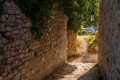 Calle de la ciudad vieja con la luz del sol en el arco de piedra fotos de archivo