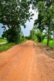 Calle de la suciedad cerca el campo de maíz del arroz Imagenes de archivo