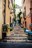 Calle de las escaleras de Taormina con las pinturas de los autores locales Fotografía de archivo
