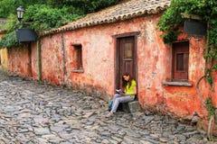 Calle de los Suspiros Street of Sighs in Colonia del Sacrament. Young woman sitting at Calle de los Suspiros Street of Sighs in Colonia del Sacramento, Uruguay stock image