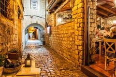 Calle de piedra en la ciudad vieja de Trogir, escena de la noche con traditi Fotografía de archivo libre de regalías