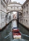 Calle de Venecia con el puente hermoso y el barco rojo imagen de archivo libre de regalías