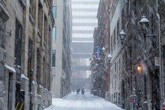 Calle de Viejo-Montreal en invierno debajo de una tormenta de la nieve con un rascacielos moderno en el fondo Imagen de archivo