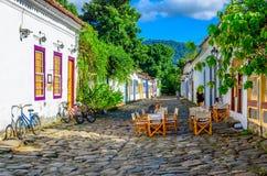 Calle del centro histórico con las tablas de restaurante en Paraty, Rio de Janeiro, el Brasil fotos de archivo