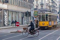 Calle del ciclista de la tranvía amarilla vieja y del hombre mayor en Milán, Italia fotos de archivo libres de regalías