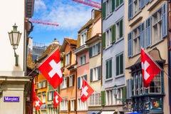 Calle estrecha con las banderas de Suiza en Zurich - Augustinergasse foto de archivo