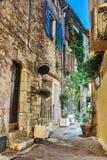 Calle estrecha con las flores en la ciudad vieja en Francia Ni Fotos de archivo