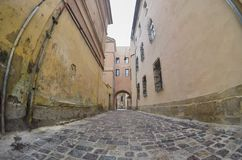 Calle estrecha con una trayectoria de las piedras de pavimentación Pase entre los edificios altos históricos viejos en Lviv, Ucra imagen de archivo libre de regalías
