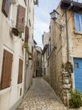Calle estrecha del adoquín en la ciudad vieja 0913 de Rovinj Foto de archivo libre de regalías