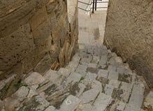 Calle estrecha en ciudad vieja con la escalera de piedra del guijarro viejo abajo imágenes de archivo libres de regalías