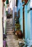 Calle estrecha entre casas brillantes viejas con las escaleras Fotografía de archivo libre de regalías