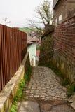 Calle estrecha entre las casas Foto de archivo libre de regalías
