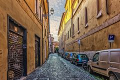 Calle italiana con los garajes de la fachada, las macetas y los edificios brillantes imagen de archivo