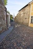 Calle larga de la piedra del adoquín en Tallinn, Estonia Imagenes de archivo