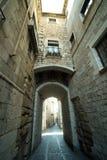Calle medieval estrecha con el arco en la ciudad de Girona, España imagenes de archivo