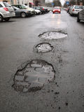 Calle mojada de la ciudad con los agujeros Foto de archivo libre de regalías