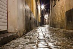 Calle mojada vieja del guijarro después de la lluvia en la noche imagenes de archivo