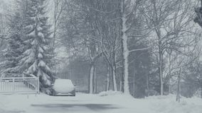 Calle Nevado de la ciudad de la montaña con el coche, calamidad de la nieve del pueblo Paisaje del invierno con nieve que cae almacen de video