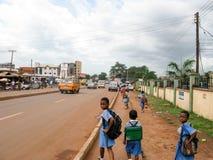 Calle nigeriana con los niños y los coches de la escuela Foto de archivo libre de regalías