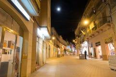 Calle nocturna iluminada de la visión con el monumento Imagen de archivo libre de regalías