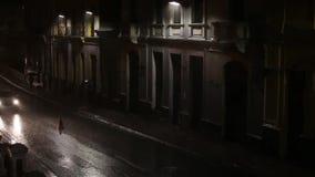 Calle oscura con pocos postes de la lámpara y coches y personas que pasan a través de las fuertes lluvias almacen de video