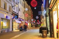 Calle peatonal iluminada por la decoración numerosa de la Navidad en el centro de ciudad del niort Imagenes de archivo