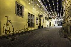 Calle que camina con las luces de la Navidad durante la noche - 6 de diciembre de 2015 en la ciudad medieval céntrica de Brasov,  Imágenes de archivo libres de regalías
