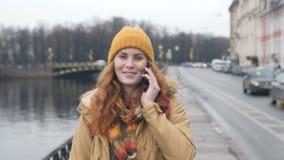 Calle que camina de la mujer caucásica roja joven del pelo que habla en el teléfono celular en ciudad almacen de metraje de vídeo