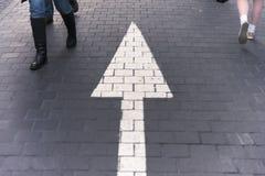 Calle que camina del pavimento de la flecha derecho con la gente que camina nosotros imágenes de archivo libres de regalías