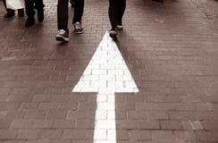 Calle que camina del pavimento de la flecha derecho con la gente que camina VI imagenes de archivo