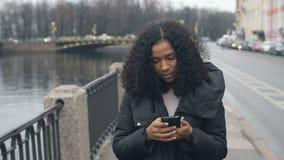 Calle que camina joven de la mujer negra del afroamericano que habla en el teléfono celular en la ciudad 4k almacen de video